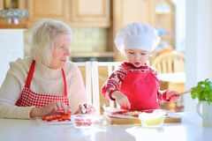 Grandmother and granddaughter preparing pizza. Happy family, grandmother with her granddaughter, adorable little girl, preparing delicious pizza together topping Royalty Free Stock Photos