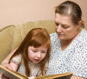 Grandmother and granddaughter read the book Stock Photos