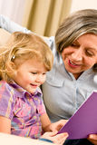 Grandmother and granddaughter read book together. Grandmother and little girl reading book happy together at home Royalty Free Stock Images