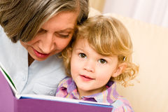 Grandmother and granddaughter read book together Stock Photo