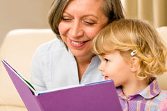 Grandmother and granddaughter read book together. Grandmother and little girl reading book happy together at home Royalty Free Stock Photography
