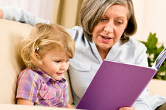 Grandmother and granddaughter read book together. Grandmother and little girl reading book happy together at home Royalty Free Stock Photo