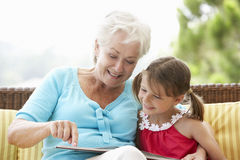 Grandmother And Granddaughter Reading Book On Garden Seat royalty free stock photos