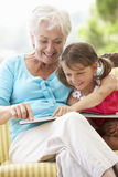 Grandmother And Granddaughter Reading Book On Garden Seat Stock Photo