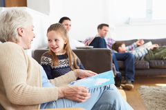 Grandmother And Granddaughter Reading Book At Home Together Stock Images