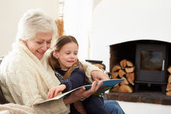 Grandmother And Granddaughter Reading Book At Home Together Royalty Free Stock Image