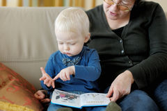 Grandmother and granddaughter reading a book Stock Images