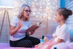 Grandmother and granddaughter are reading children`s book at night at home. Grandmother and granddaughter are reading children`s book sitting on bed at night at Stock Photography