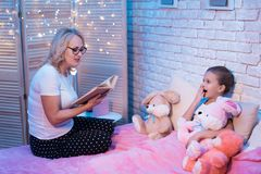 Grandmother and granddaughter are reading children`s book at night at home. Grandmother and granddaughter are reading children`s book sitting on bed at night at Stock Photo
