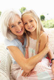 Grandmother With Granddaughter Relaxing Together. Portrait Of Grandmother With Granddaughter Relaxing Together On Sofa Royalty Free Stock Photography