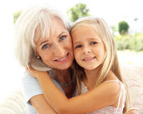 Grandmother With Granddaughter Relaxing Together. Portrait Of Grandmother With Granddaughter Relaxing Together On Sofa Royalty Free Stock Image