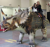 A Grandmother and Granddaughter Ride a Styracosaurus at T-Rex Pl Royalty Free Stock Images
