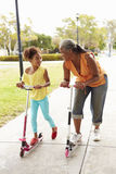 Grandmother And Granddaughter Riding Scooters In Park Royalty Free Stock Photos