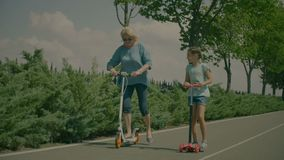 Grandmother and granddaughter riding scooters in park stock footage