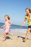 Grandmother And Granddaughter Running Along Beach Stock Photos