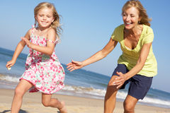 Grandmother And Granddaughter Running Along Beach. Grandmother And Granddaughter Having Fun Running Along Beach Royalty Free Stock Images