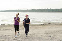 Grandmother and granddaughter running together. On lake shore Royalty Free Stock Images