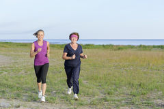 Grandmother and granddaughter running together. On lake shore Royalty Free Stock Photo