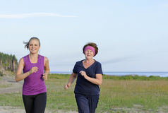 Grandmother and granddaughter running together. On lake shore Stock Photo