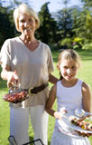 Grandmother and granddaughter (8-10) serving barbecued food in garden, girl holding plate of kebabs, woman holding hamburger with  Stock Photo