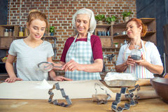 Grandmother and granddaughter sifting flour stock photo