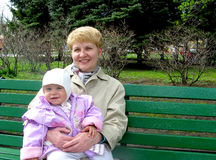 The grandmother with the granddaughter sit on a bench in park Stock Photos