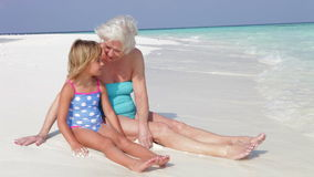 Grandmother And Granddaughter Sitting On Beautiful Beach stock video footage