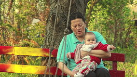 Grandmother And Granddaughter Sitting On A Bench stock video footage