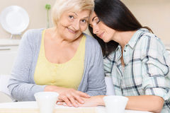 Grandmother and granddaughter sitting in kitchen Royalty Free Stock Photography