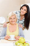 Grandmother and granddaughter sitting in kitchen Stock Image