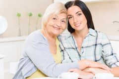 Grandmother and granddaughter sitting in kitchen Stock Photography