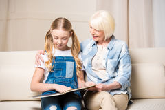 Grandmother and granddaughter sitting on sofa and looking at photo album royalty free stock image