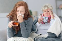 Grandmother and granddaughter with flu. Grandmother and granddaughter sitting together with common flu during autumn weather Royalty Free Stock Photos