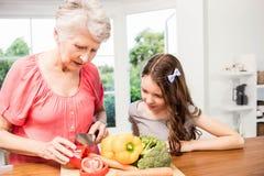 Grandmother and granddaughter slicing vegetables Stock Images