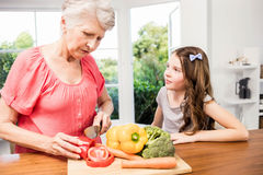 Grandmother and granddaughter slicing vegetables Royalty Free Stock Photo