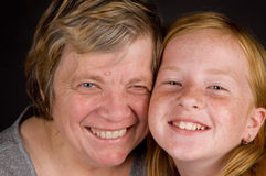 Grandmother and granddaughter smiling. Grandmother and granddaughter happily smiling stock images