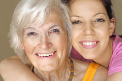 Grandmother and granddaughter smiling. Grandmother and granddaughter portrait, embraced , with a great smile Stock Images