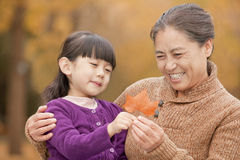 Grandmother and granddaughter smiling and looking at leaf together Stock Photo