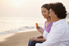 Grandmother and Granddaughter Smiling and Looking At Seashell Royalty Free Stock Images