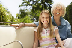 Grandmother And Granddaughter On Sofa In Back Yard. Portrait of happy girl with grandmother sitting on sofa in backyard Royalty Free Stock Images