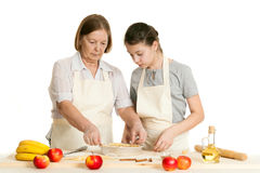 The grandmother and the granddaughter stack dough strips Stock Images