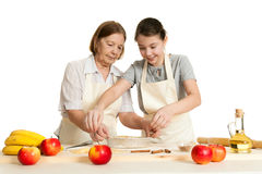 The grandmother and the granddaughter stack dough strips Stock Image