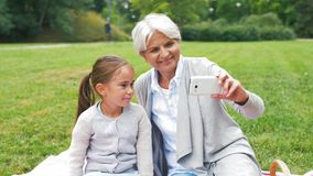 Grandmother and granddaughter take selfie at park stock video