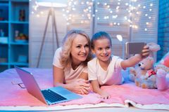 Grandmother and granddaughter are taking selfie at night at home. royalty free stock photos