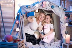 Grandmother and granddaughter are taking selfie in blanket house at night at home. royalty free stock photo