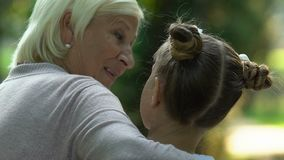 Grandmother and granddaughter talking and hugging, sitting on bench, back view stock video
