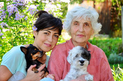 Grandmother and granddaughter with their dogs Royalty Free Stock Photos