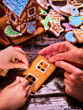 Grandmother and granddaughter together make a gingerbread house for Christmas. Royalty Free Stock Images