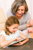 Grandmother with granddaughter use touch tablet Royalty Free Stock Photography