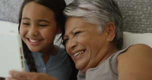 Grandmother and granddaughter using digital tablet in bed room 4k. Grandmother and granddaughter using digital tablet in bed room at home 4k stock video